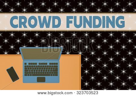 Word writing text Crowd Funding. Business concept for Fundraising Kickstarter Startup Pledge Platform Donations Upper view office working place laptop lying wooden desk smartphone side. poster
