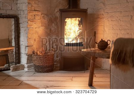 Table And Teapot Near Wood Stove Fireplace In Comfort House With Cozy Interior In Room. Wicker Baske