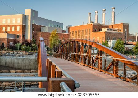 footbridge over Cache la Poudre River at newly constructed whitewater park in downtown of Fort Collins Colorado with Powerhouse Energy Campus of Colorado State University in background