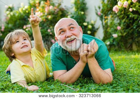 Child With Grandfather Dreams In Summer In Nature. Happy Child With Grandfather Playing Outdoors. Gr
