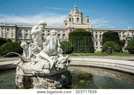 Antique White Fountain With Sculptures On The Background Of The Naturhistorisches Museum Wien. Maria