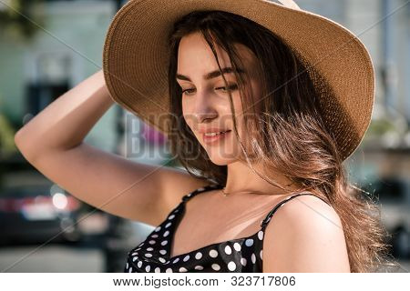 Pretty Girl In A Black Dress And A Hat With Wide Flaps Smiles Enjoying Walk Down The European Town D