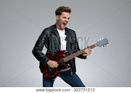 side view of a gorgeous casual man with black leather jacket standing and playing his guitar thrilled on gray studio background