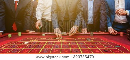 Group Of People Behind Roulette Gambling Table In Luxury Casino. Friends Playing Poker At Roulette T