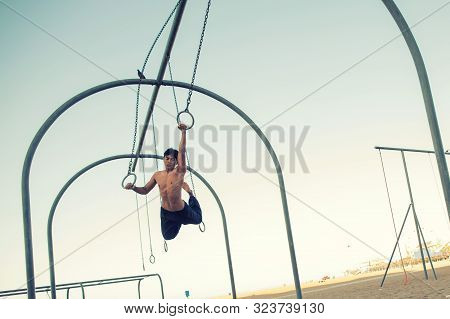 A young man athlete working out on traveling rings on muscle beach, Santa Monica, California poster