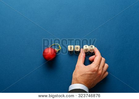 Red Holiday Bauble Next To A 2019 Sign On Wooden Dices With Male Hand Turning The Last Two Dices To