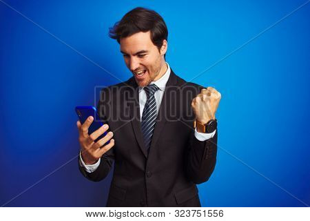 Young handsome businessman using smartphone standing over isolated blue background screaming proud and celebrating victory and success very excited, cheering emotion