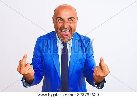 Middle age businessman wearing suit standing over isolated white background Showing middle finger doing fuck you bad expression, provocation and rude attitude. Screaming excited