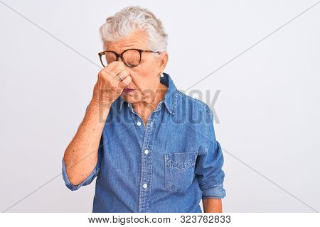 Senior grey-haired woman wearing denim shirt and glasses over isolated white background tired rubbing nose and eyes feeling fatigue and headache. Stress and frustration concept.