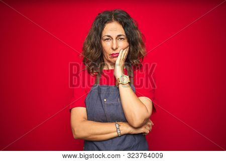 poster of Middle age senior woman wearing apron uniform over red isolated background thinking looking tired and bored with depression problems with crossed arms.