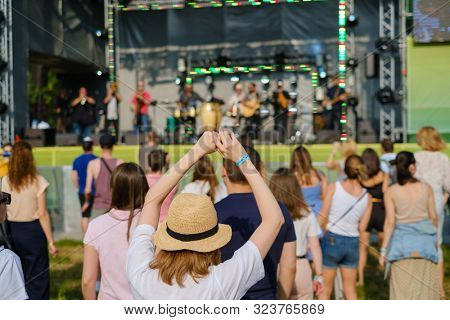 Girls friends watching concert at open air music festival, rear view, stage and spectators at background