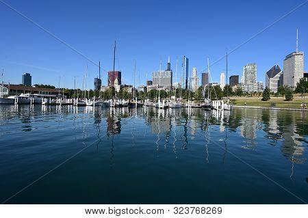Chicago, Illinois - August 9, 2019 - Chicago Yacht Club And City Skylone Reflected In Calm Lake Mich