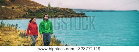Panoramic travel banner of hikers tourists couple walking by nature lake in New Zealand tramping active lifestyle. Panorama people traveling.