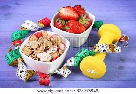 Fresh Ripe Strawberries With Wheat And Rye Flakes, Dumbbells For Fitness And Tape Measure, Concept O