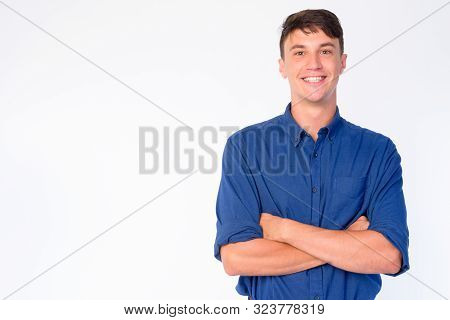 Portrait Of Happy Young Handsome Businessman With Arms Crossed