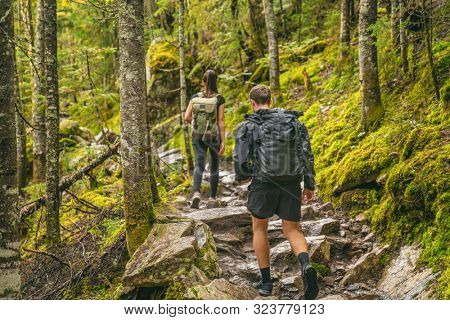 Hike couple hikers hiking forest trail in Autumn nature going camping with backpacks. Friends woman and man walking uphill on mountain in Quebec travel, Canada.