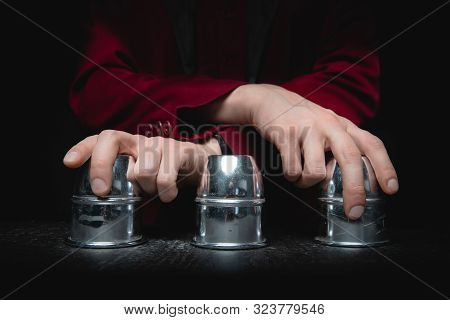 Magician Shows Shell Game Of Thimbles With Circles And Ball, Black Background. Concept Deception, Sl