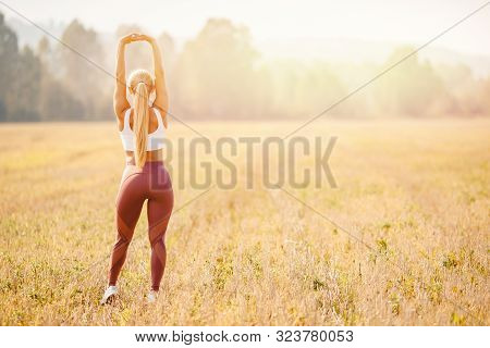 Young Woman Blonde In Red Pants And White T-shirt Performs Warm Before Running In Park