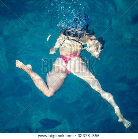 A Girl Swims In The Blue Water Of The Sea.