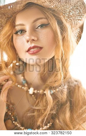 Portrait of a beautiful smiling girl with red hair. Bright light in the background. Hippie and modern bohemian style.
