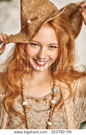 Portrait of a beautiful laughing girl with red hair. Beauty and make-up concept. Hippie style. Bohemian style.