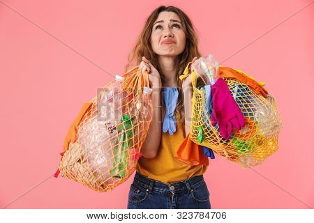 Photo of unhappy young woman in basic t-shirt holding bags with plastic waste and looking upward isolated over pink background