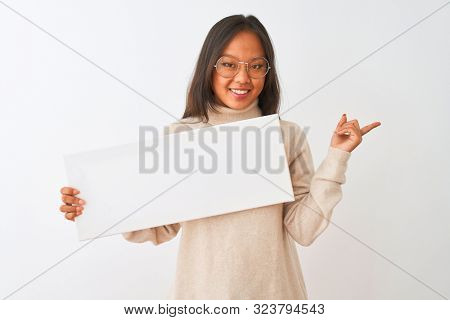 Young beautiful chinese woman wearing glasses holding banner over isolated white background very happy pointing with hand and finger to the side