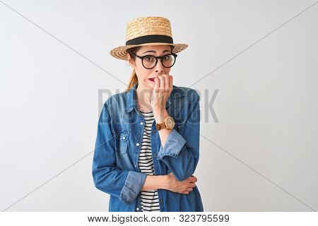 Redhead woman wearing denim shirt glasses and hat over isolated white background looking stressed and nervous with hands on mouth biting nails. Anxiety problem.