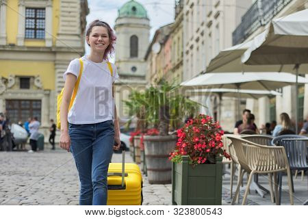 Girl Teenager Student Walking With Backpack And Yellow Suitcase On City Street. Start Of Studies, Mo