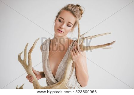 Young Beautiful Woman Posing With Big Horns In A Studio On White Background