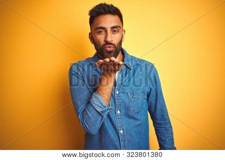 Young indian man wearing denim shirt standing over isolated yellow background looking at the camera blowing a kiss with hand on air being lovely and sexy. Love expression.