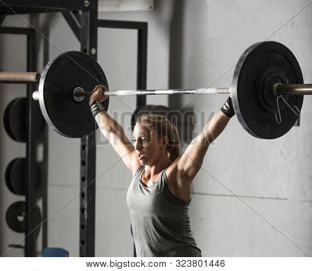 Close up of strong young woman lifting barbell over her head in gym.