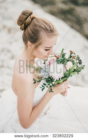 Young Beautiful Bride Posing With Wedding Bouquet With Gorgeous Nature View On The Background.