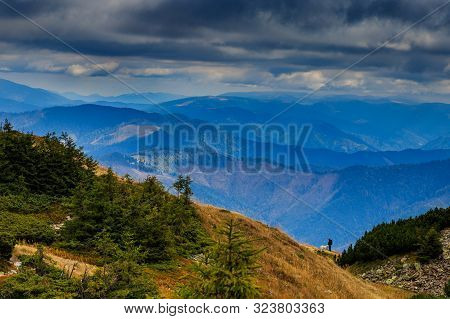 Hiker With A Dog Admire The Autumn Mountain Landscape At The Top Of Mount Strymba Near The Village O
