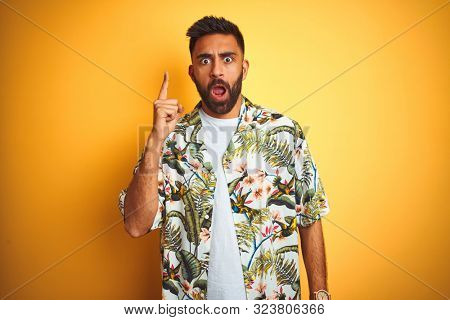 Young indian man on vacation wearing summer floral shirt over isolated yellow background pointing finger up with successful idea. Excited and happy. Number one.