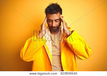 Young indian man wearing raincoat standing over isolated yellow background with hand on head for pain in head because stress. Suffering migraine.