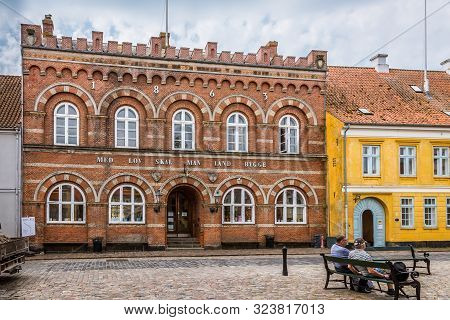 Two Men Sitting On A Bench In Front Of The Townhall In Ærøskøbing, Denmark, July 13, 2019