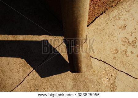 Downpipe at the corner of the building, cracks in the blind area of the house, sunlight and shadow from the drain pipe poster