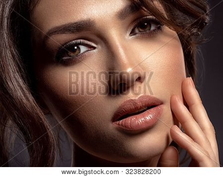 Beautiful woman with brown hair. Attractive model with brown eyes. Fashion model with a smokey makeup. Closeup portrait of a pretty woman looks at camera. Sexy woman.
