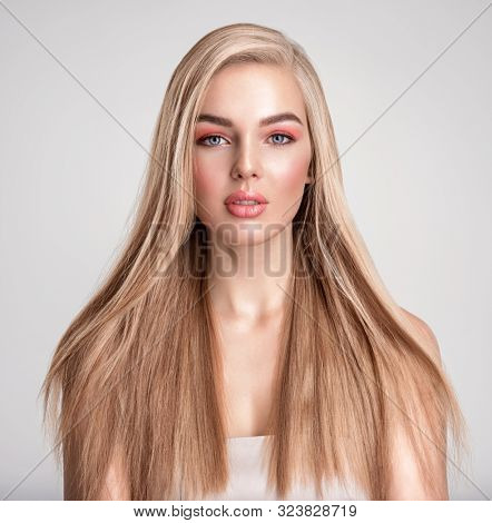 Portrait of a blonde beautiful woman with a long straight light hair. Portrait of a beautiful woman with a coral color makeup. Girl with  bright fashion make-up. Beautiful female face. Fashion model.