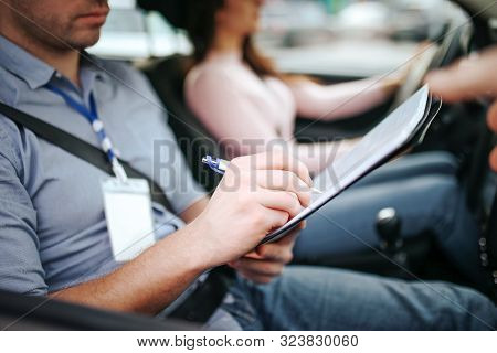 Male Auto Instructor Takes Exam In Young Woman. Close Up Of Man Writing On Paper. Passing Practical