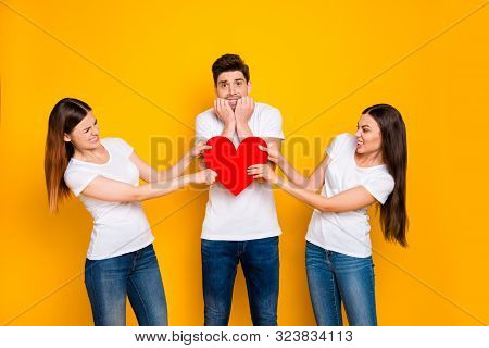 Portrait of two nice attractive lovely lovable competitive irritated fury girlfriends taking pulling one heart contest family desire isolated over bright vivid shine yellow background poster