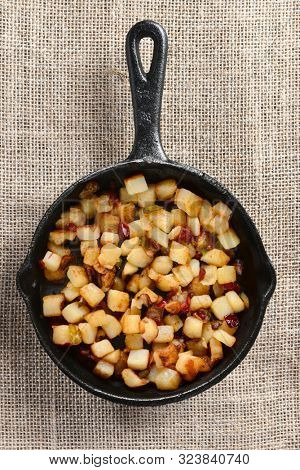 High angle shot of Fried Breakfast Potatoes in a cast iron skillet. Peppers, onions and potato cubes fill the skillet on burlap.