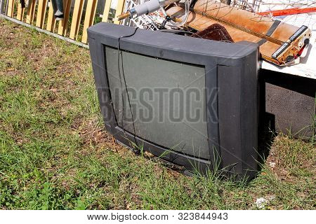 Old Tv Set Dumped And Left In Garden Along With Other Bulky Trash. Old Tv Thrown Away Next To A Wall