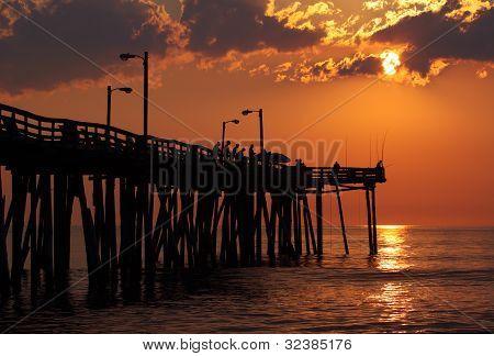 Fishermen At Sunrise On A Fishing Pier In North Carolina