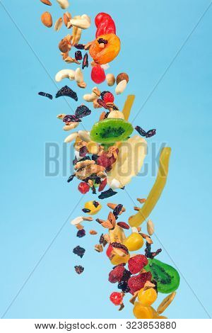 Dried And Candied Fruits And Nuts Flying On Blue Background. Stock Photo Of Healty And Nutrient Food