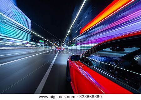 View From Side Of A Red Muscle Car Moving In A Night City, Blured Road With Lights With Car On High