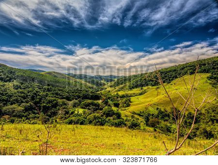 A Valley In Secretário, Rio De Janeiro, Brazil, On A Sunny Day With Clouds And Blue Sky Viewed From