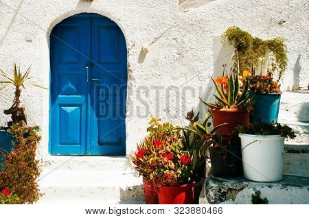 The entrance to a traditional greek house with blue gates and a whitewashed wall, and colourful plants to welcome visitors