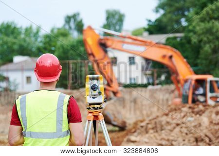 surveyor worker with theodolite at construction site